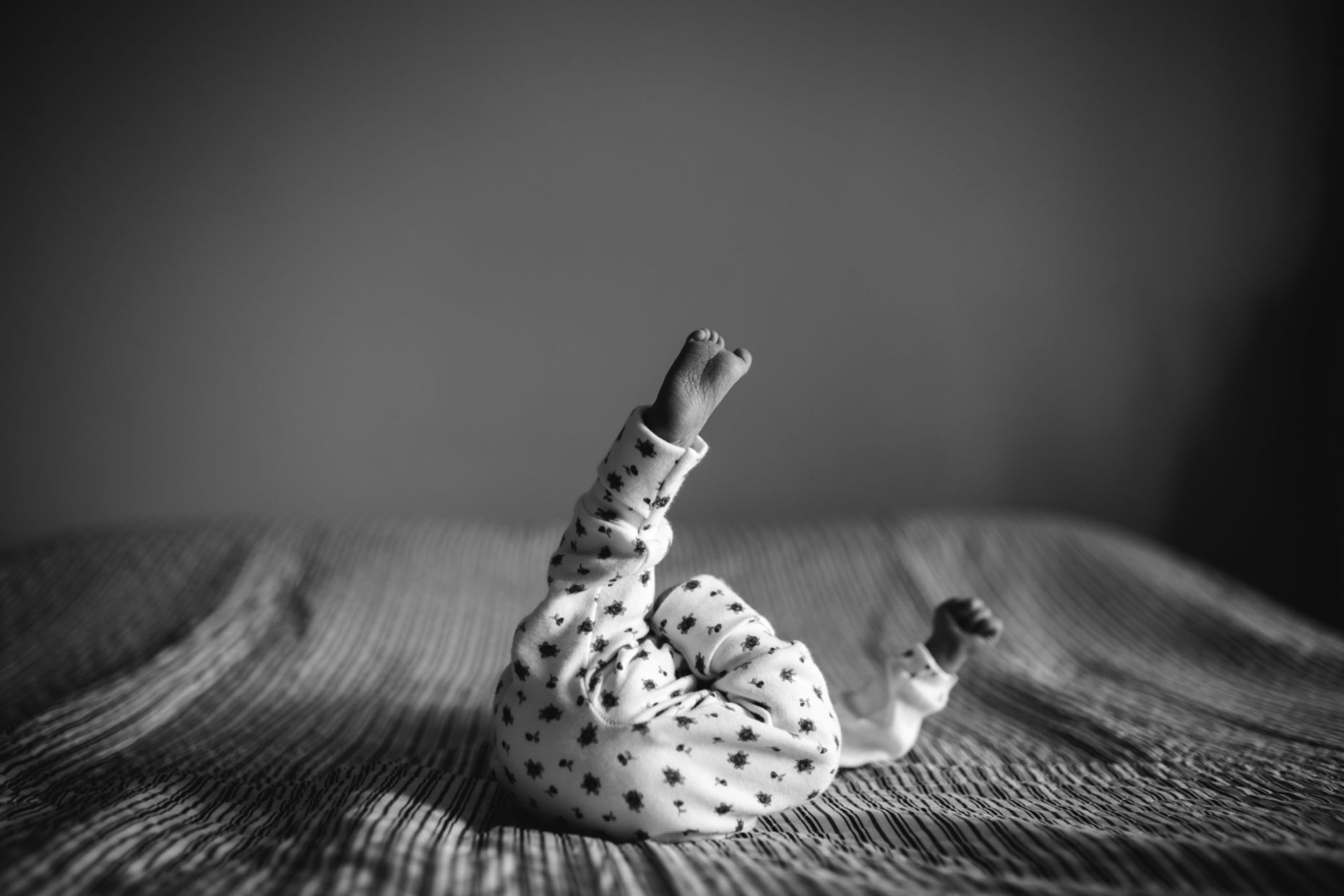 black and white photography of a newborn baby lying on a bed, wearing a white body with a little hearts pattern. She is stretching one leg, pointing to the roof