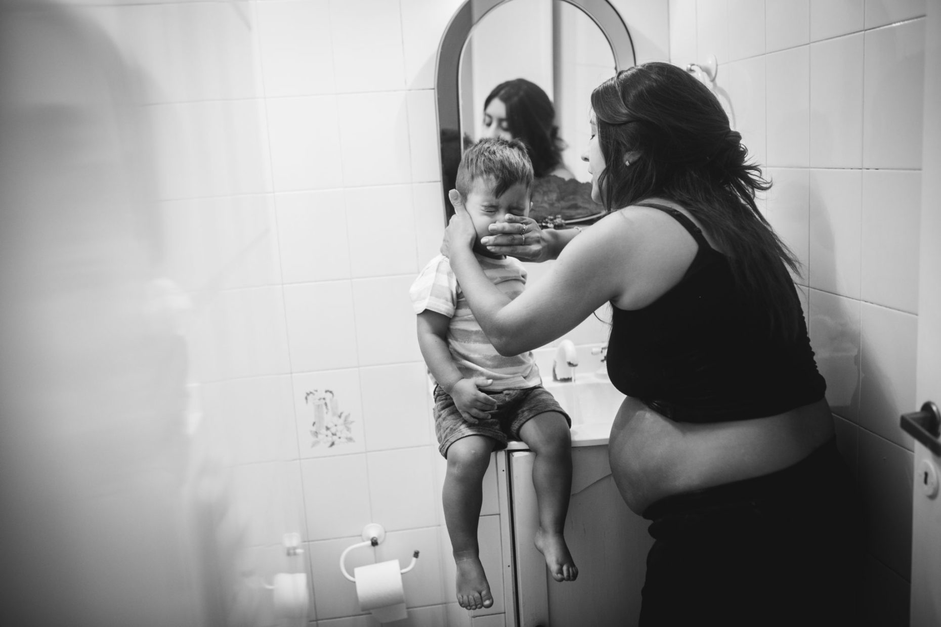 Photo of a pregnant mom cleaning her toddler face in the bathroom. Natural style of maternity photography in Amsterdam.