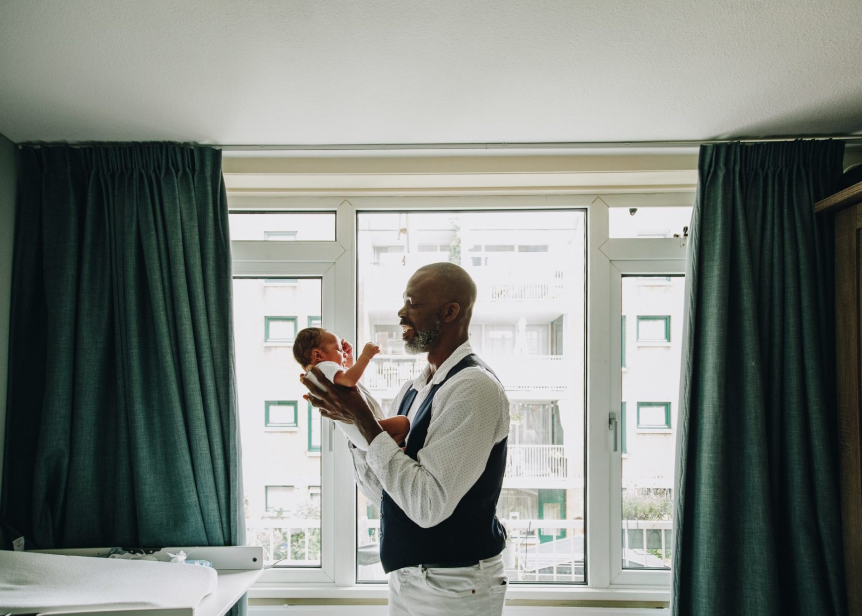 Backlighting. Dad holding his newborn baby next to the window.