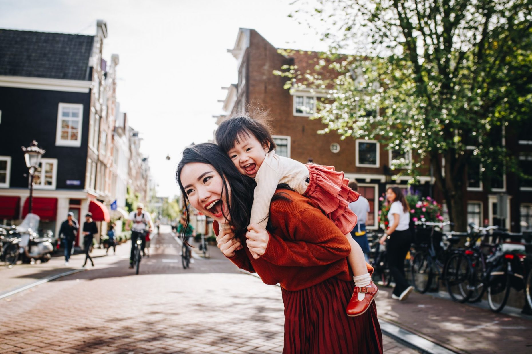 mom and her child on her back, playing on the streets of Amsterdam on a Saturday morning