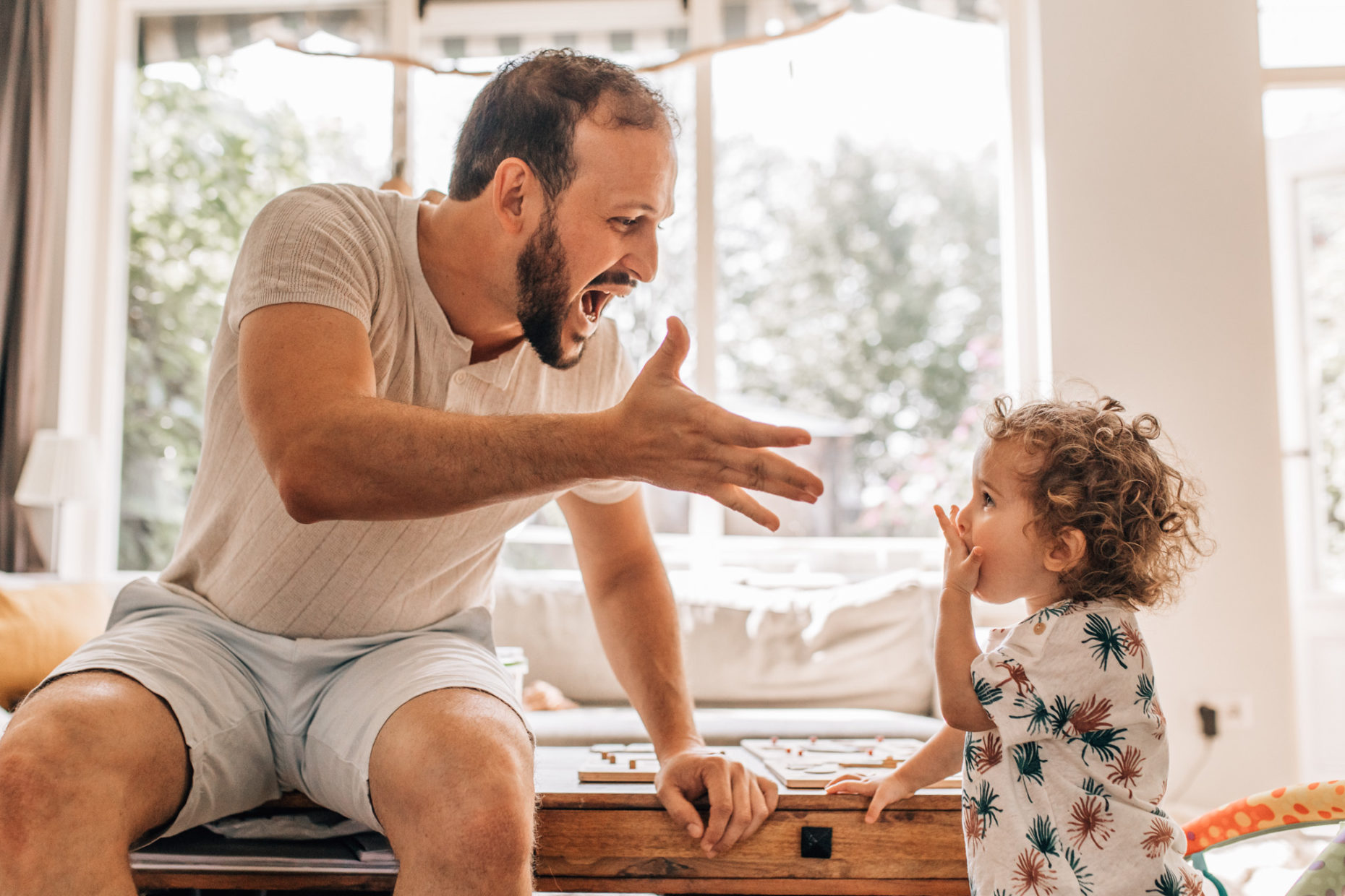 Dad playing with his little daughter, sending kisses to the air