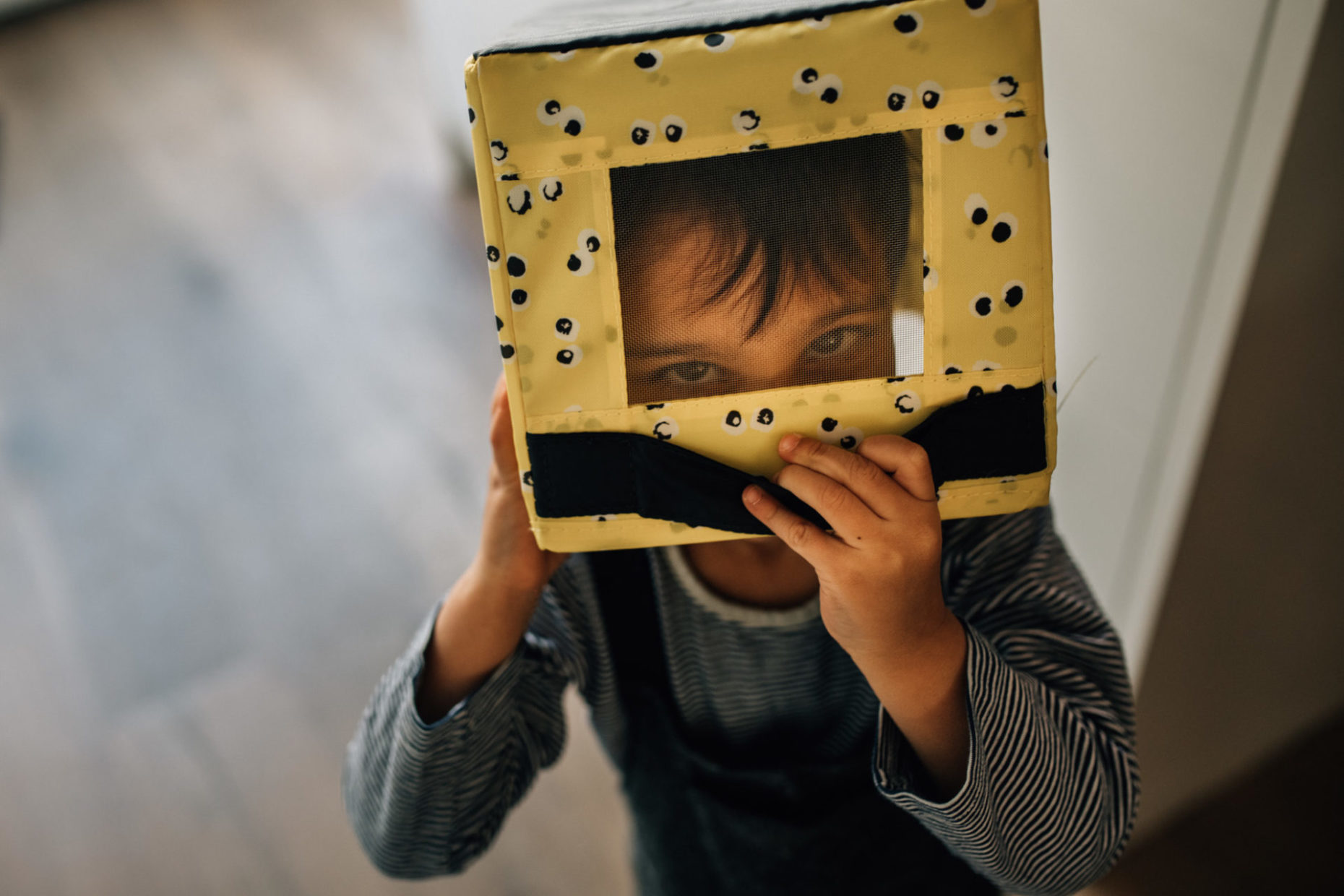 Child with a box on his head, his eyes are looking at the camera. Amsterdam portrait.