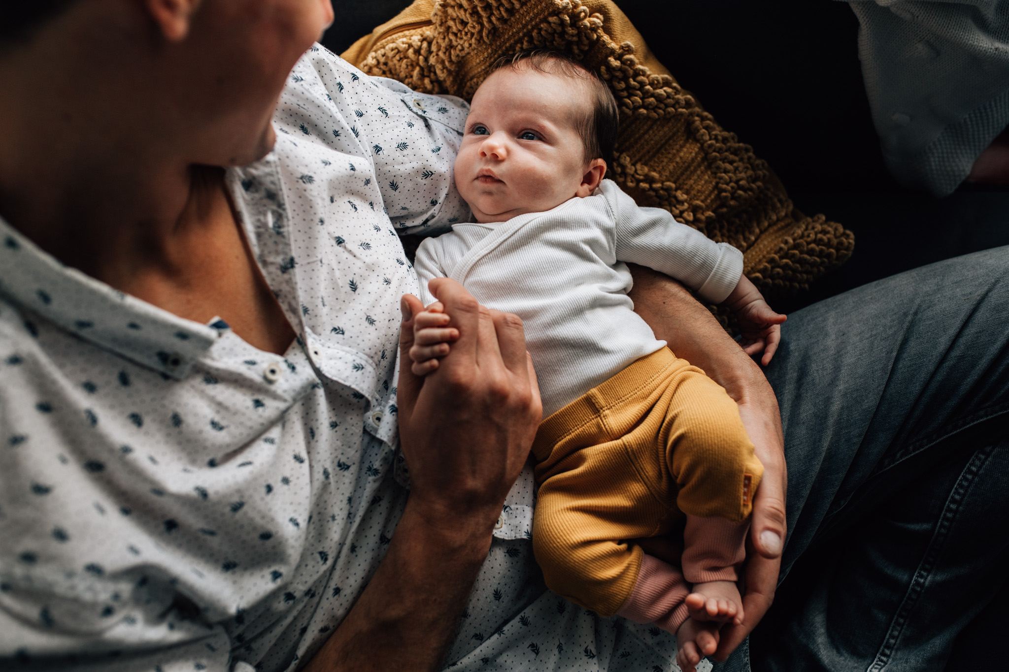 Portrait of a newborn baby being hold by her dad on his lap. Baby girl contemplating at him, while holding his hand.