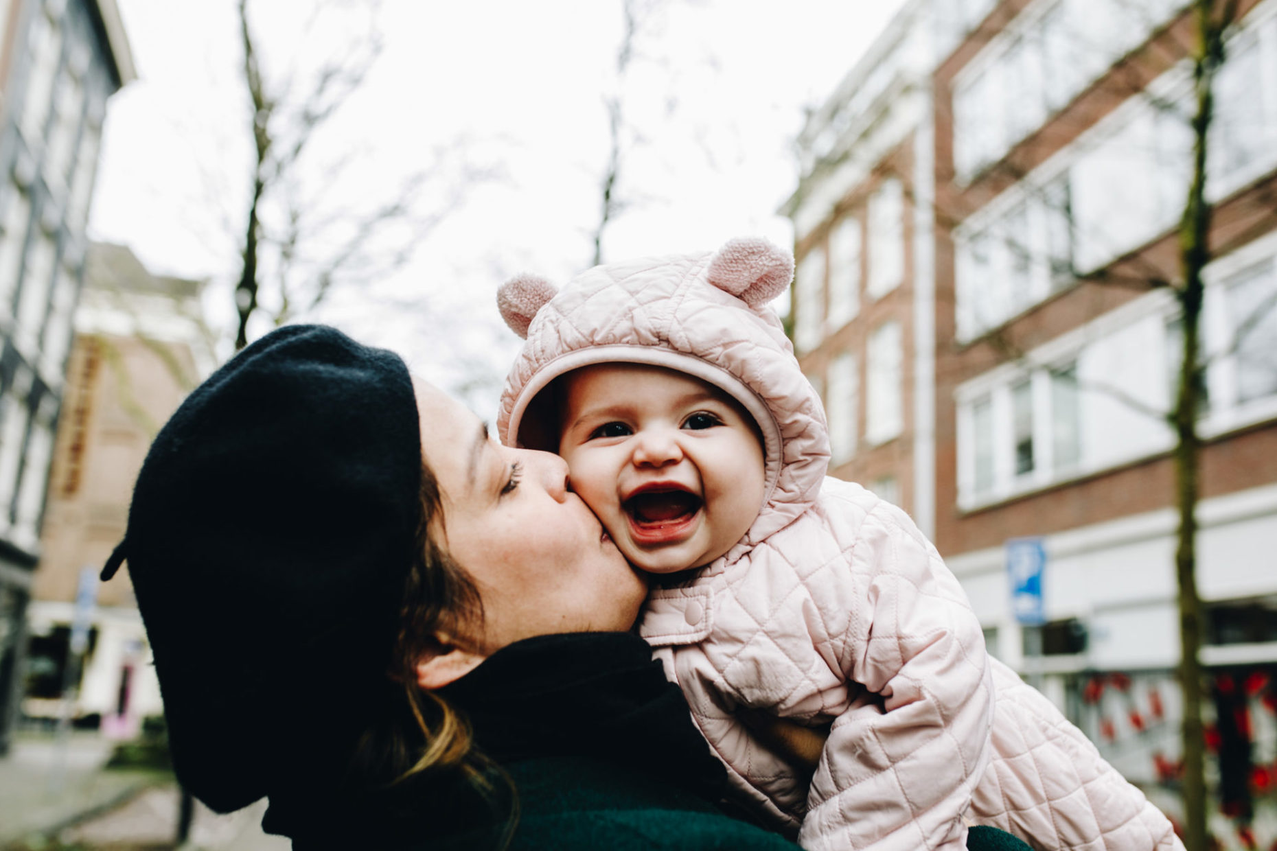 Mom kissing baby's cheek. Baby has an amazing huge smile on her face. Outdoor during the winter. De Pijp.