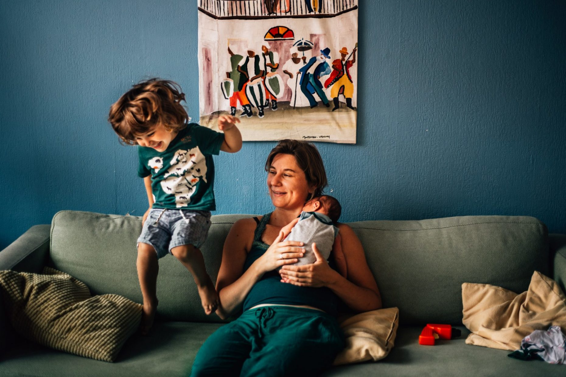 Toddler jumping on the couch where his mom is sitting holding her newborn baby. Newborn photography Amsterdam with siblings