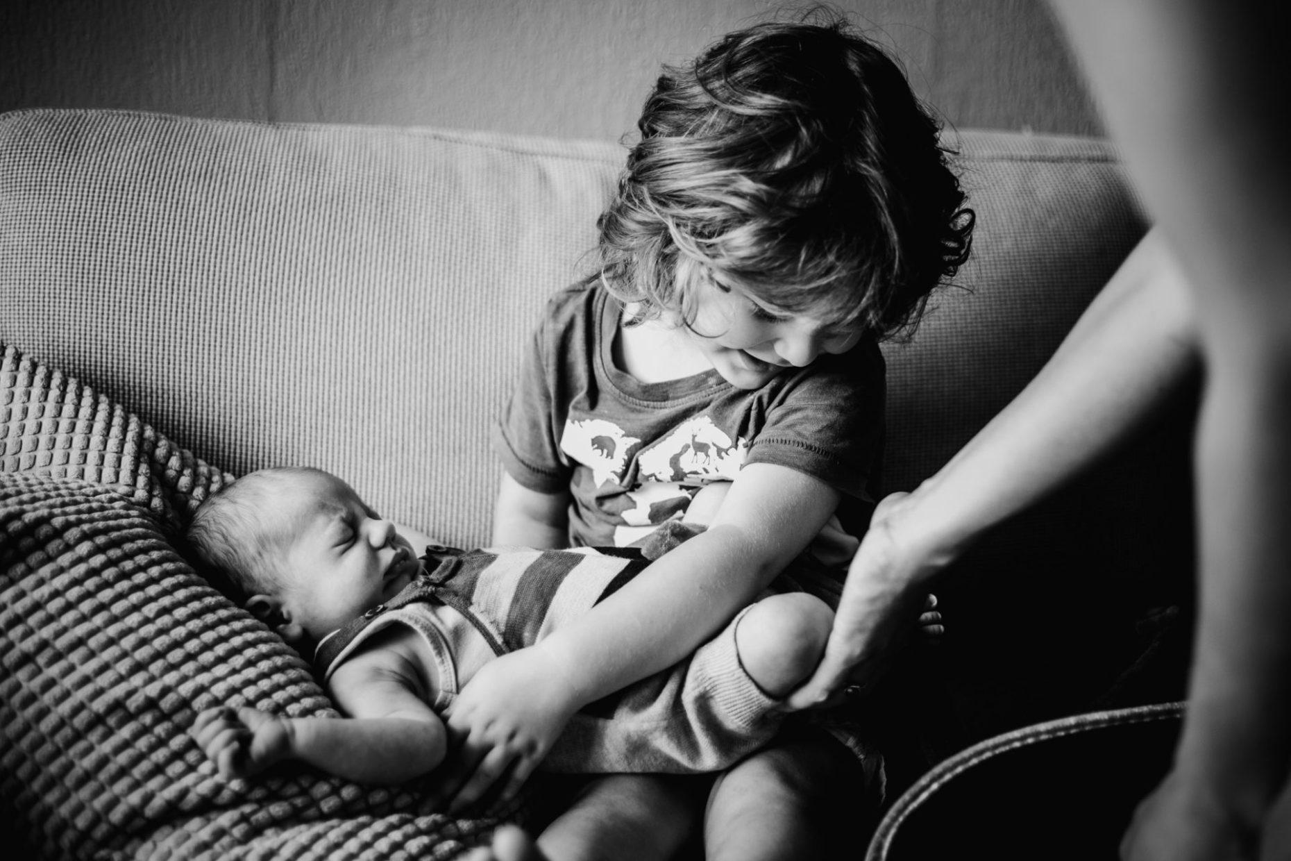 EN: Little boy (aprox 2 years old) holding his newborn brother for the first time. They're sitting on a couch. Moms hand is there helping him. Black and white photography. NL: Klein kind dat voor het eerst zijn pasgeboren broertje vasthoudt. Mama helpt hem daarbij. Baby fotografie.