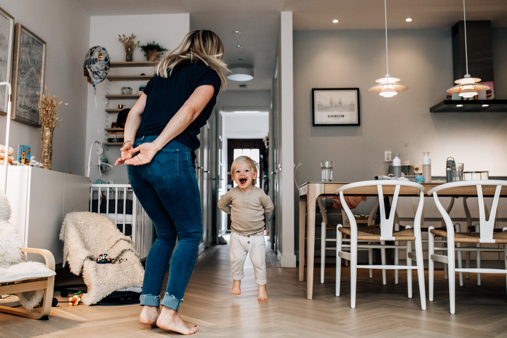 Mom and toddler jumping together in the kitchen