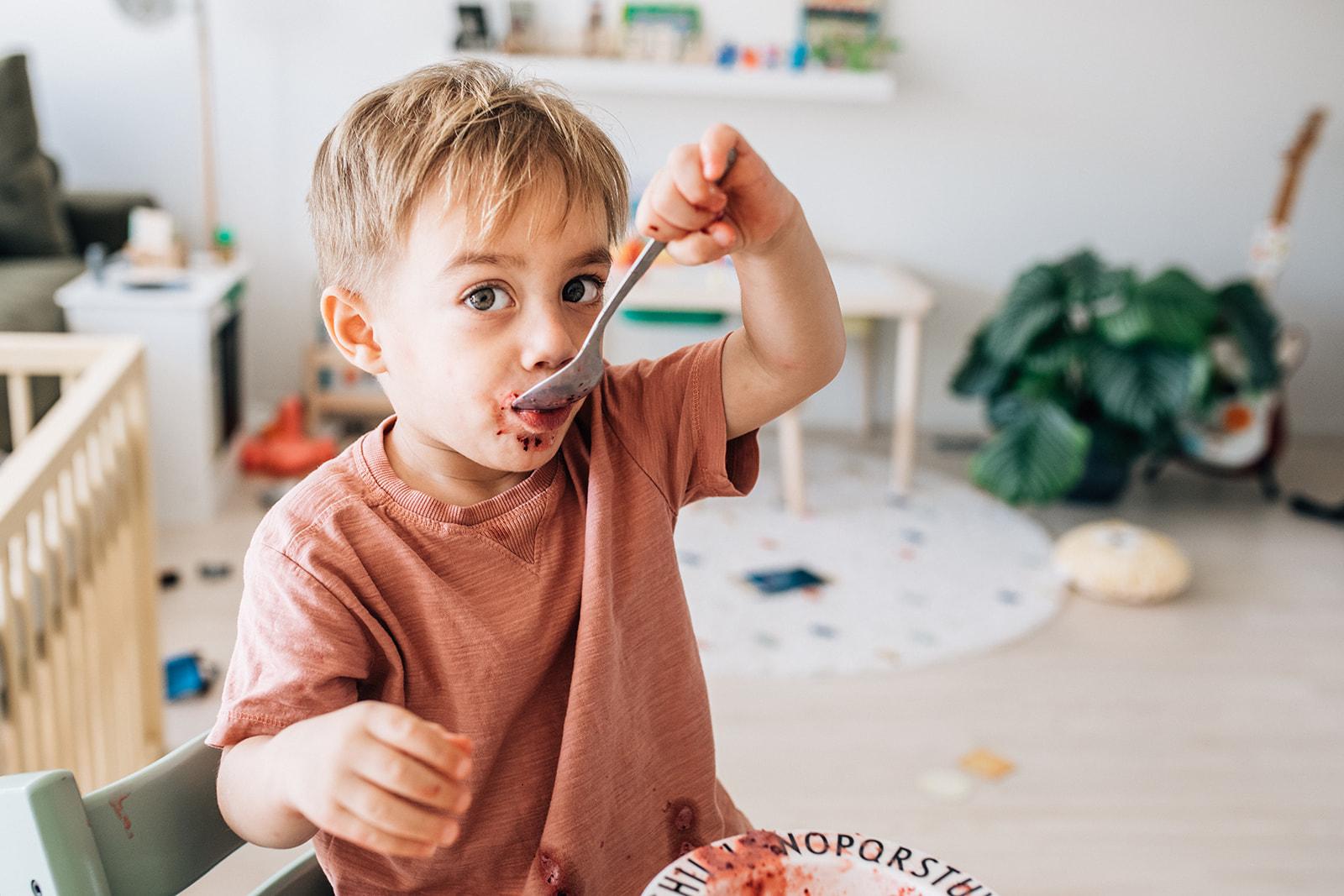 kid eating a messy pink desert
