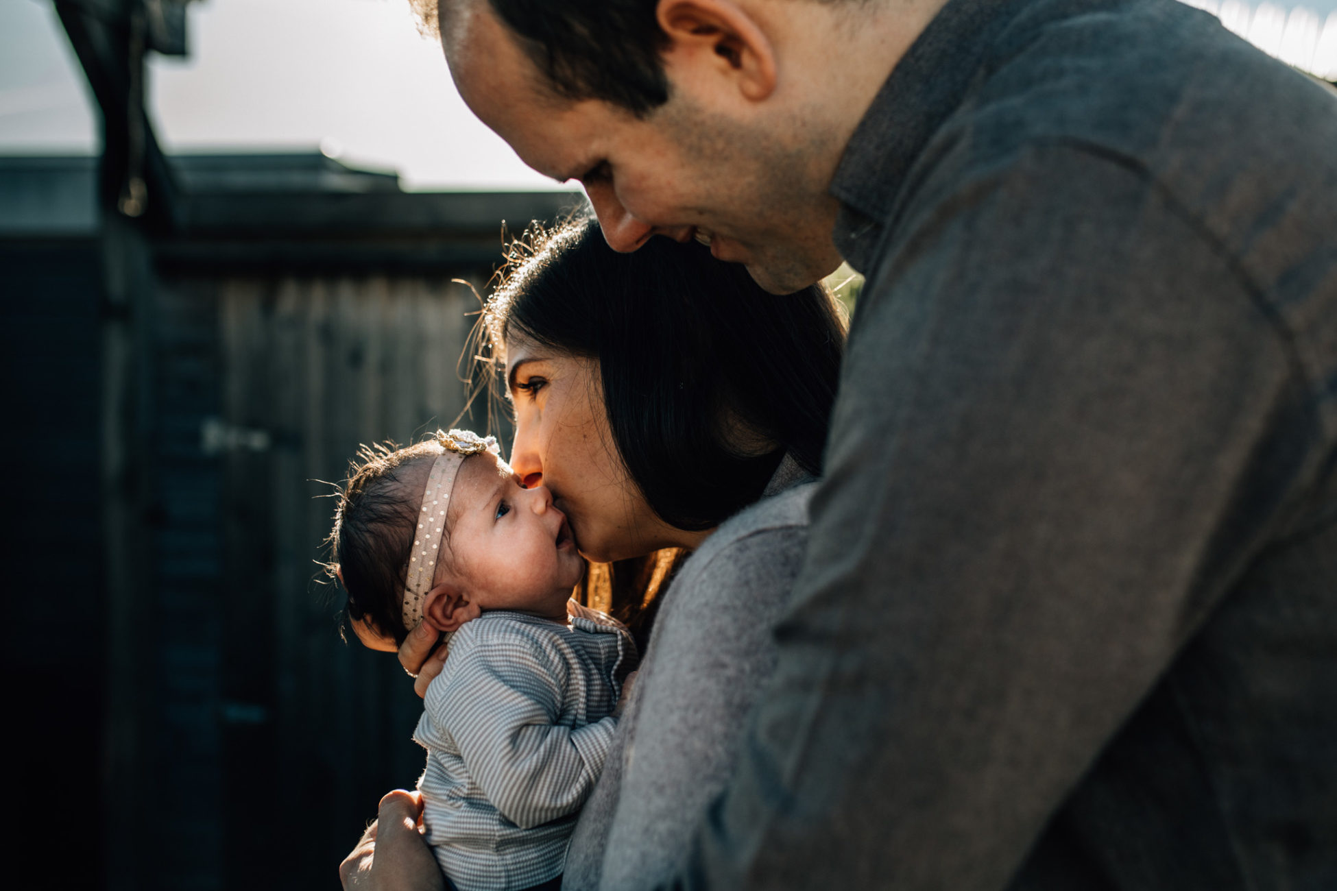 Outdoors photography. Mom holding and kissing her newborn girl while dad is hugging them
