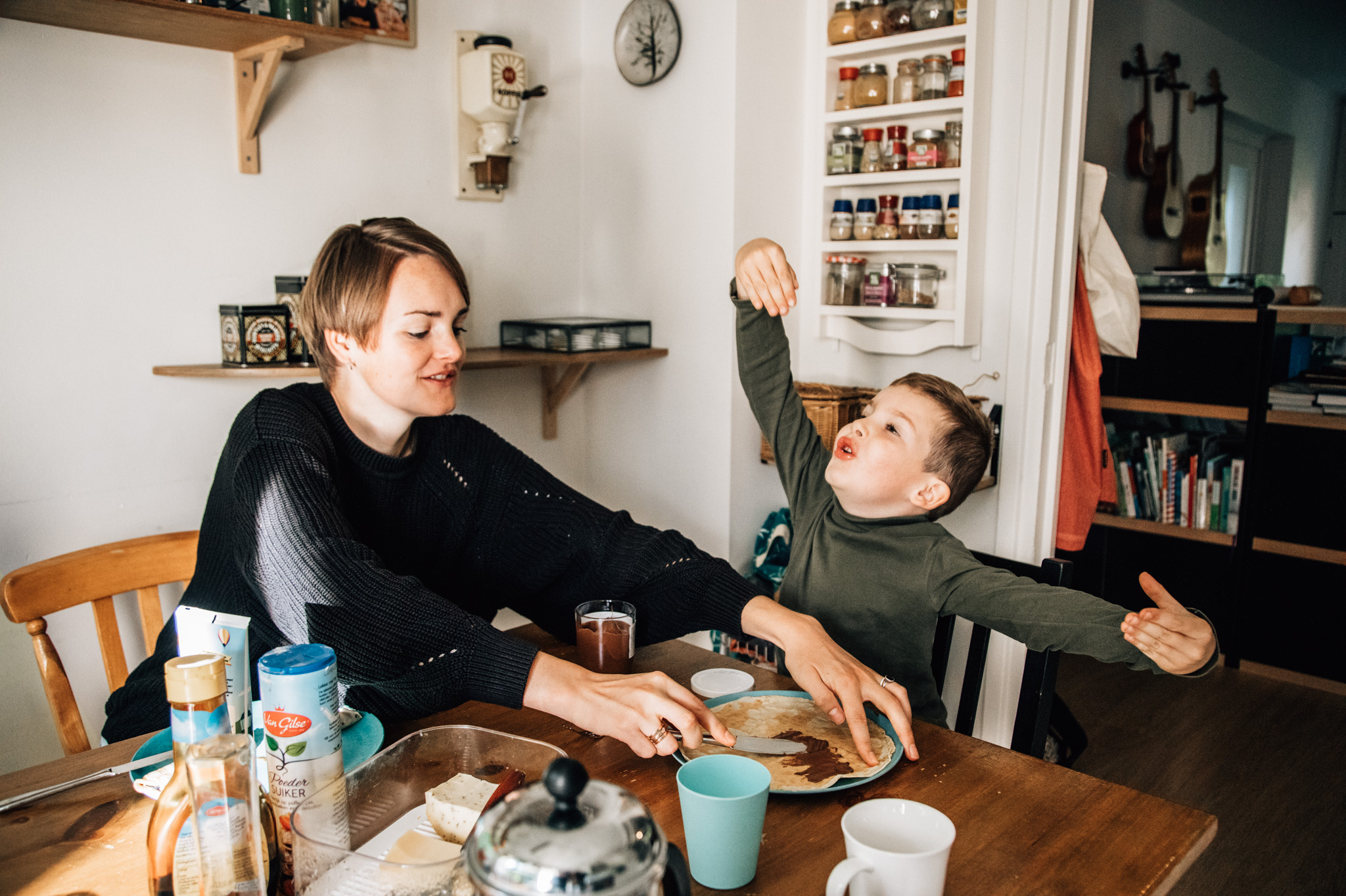 Things you can do during your family photoshoot: to have breakfast together: Mom and child having breakfast together in the kitchen. Kid has arms wide open, like talking of a big explosion while his mom is spreading nutella on his pannenkoek