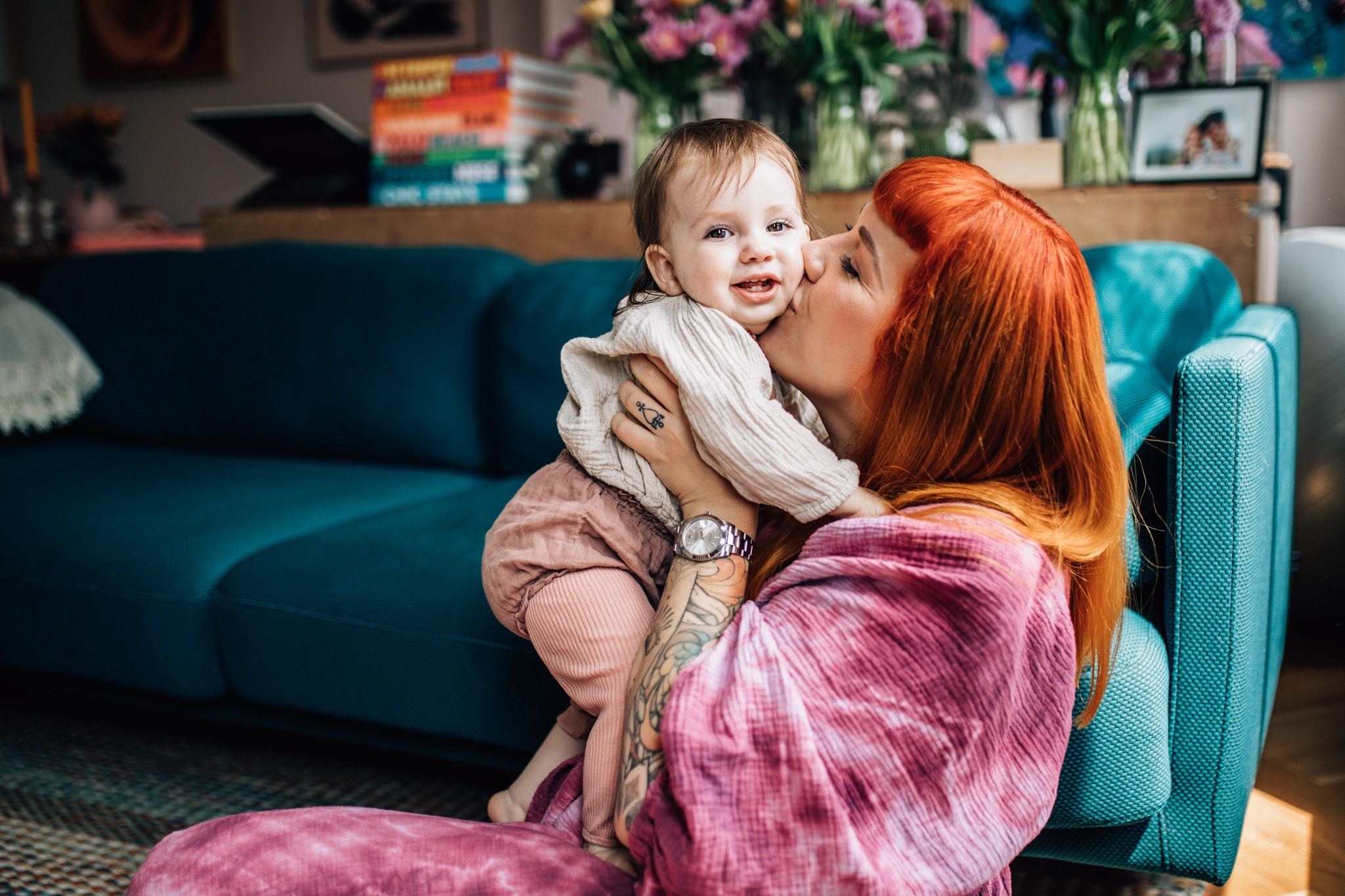 Mom kissing her little girl on her cheek. They're sitting on the floor of their livigroom. Mom is wearing a purple hand dyed dress, she has amazing orange hair and some tattoos on her arm and hand. The photoshoot took place in their home, in Amsterdam.